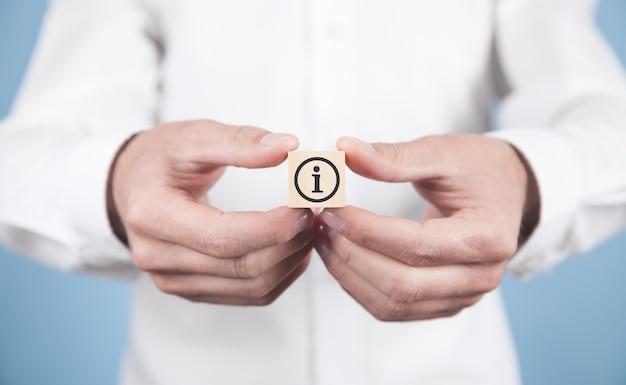 木製の立方体に情報シンボルを示す男