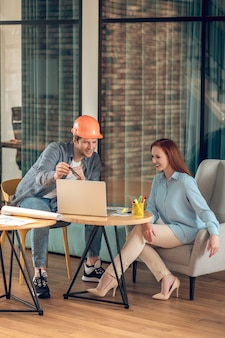 웃는 여자에게 노트북 화면을 보여주는 남자