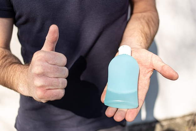 Man showing like and holding a bottle of antibacterial sanitizer