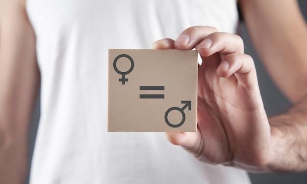 Мужчина показывает мужские и женские символы на деревянной доске. концепция гендерного равенства