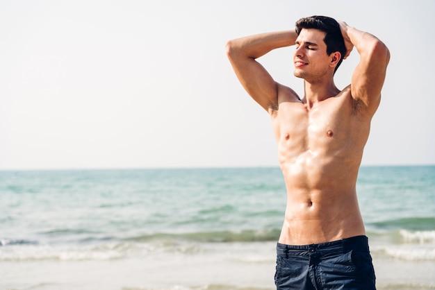 Человек показывает мускулистое тело в форме стоя на пляже