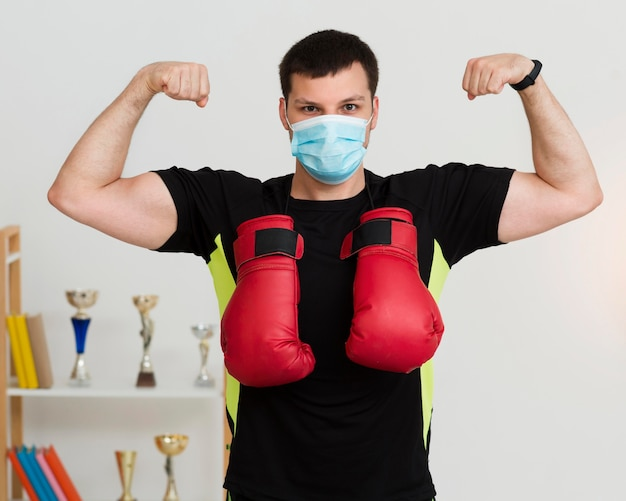 Man showing off his muscles while wearing a medical mask
