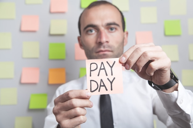 付箋紙に給料日のテキストを表示している男。