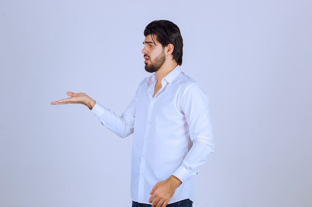 Man showing and pointing left side.