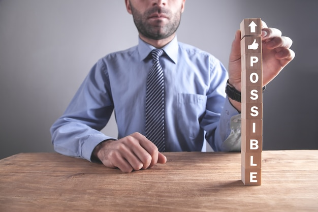 木製の立方体に可能な単語を示す男。