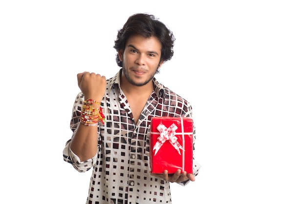 Man showing rakhi on his hand with shopping bags and gift box on the occasion of raksha bandhan festival.