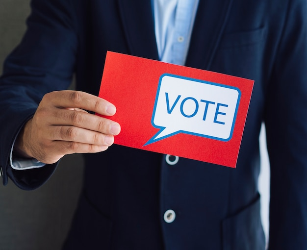 Man showing a red ballot to the camera