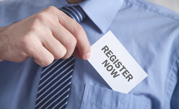 Man showing register now text in business card.