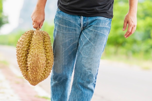 Man showing ripe durian happily
