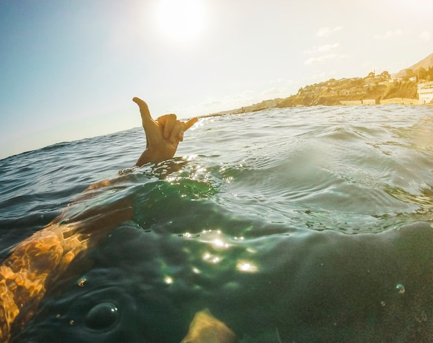 Человек показывая знак руки shaka в открытом море