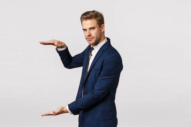 Man showing something big. attractive bearded blond businessman in classic suit, hold hand as holding something, shaping large object, diagram, showing amount money can gain, white wall