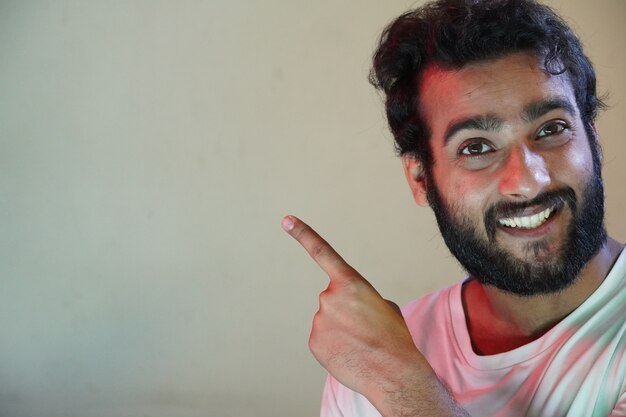 Человек, показывающий что-то в левой стороне, используя руку, портрет красивого молодого человека улыбается