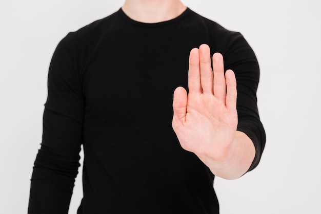 Man showing stop gesture over white background