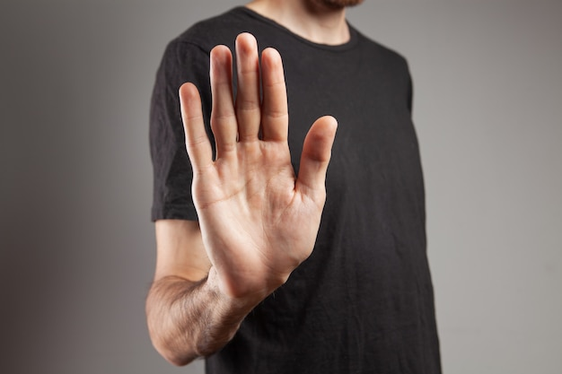 彼の手で停止を示している男