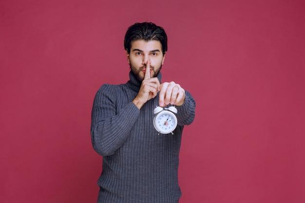 알람 시계를 표시하고 침묵을 요구하는 남자.