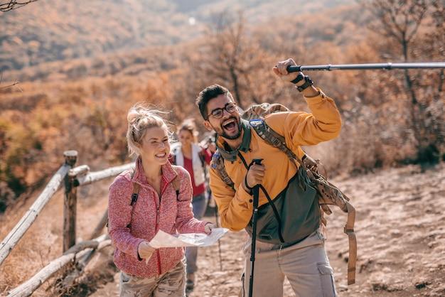Укомплектуйте личным составом показывать путь и женщину держа карту пока взбирающся холм.