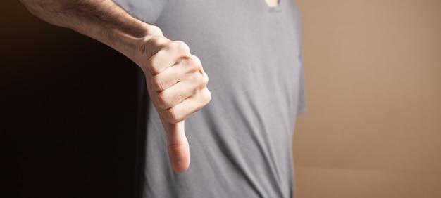 茶色の背景に親指を下に示す男