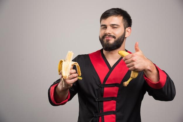 親指を立てて灰色の表面にバナナを食べる男。