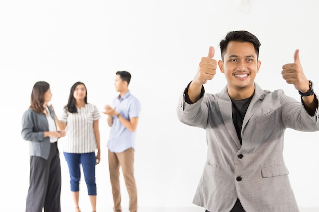 Man showing thumb up in front of his team