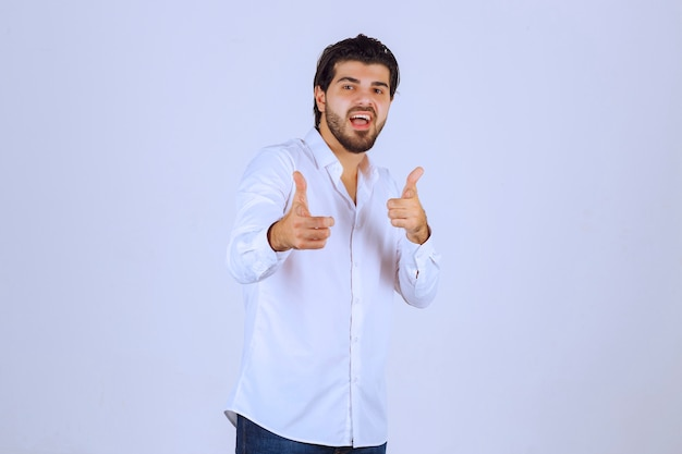親指を立てる手のサインを示す男。