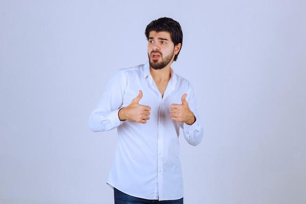 Человек показывает палец вверх по знаку руки.