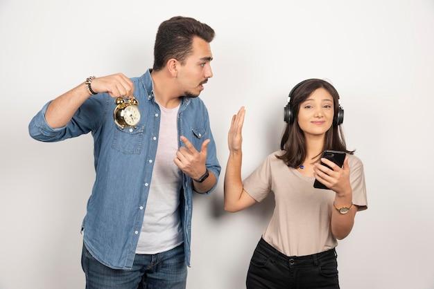 Uomo che mostra il tempo a una donna disinteressata che ascolta una canzone.