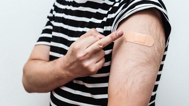 ワクチン接種された腕を示す男。予防接種の概念。ワクチン接種後に包帯で腕を見せている人。