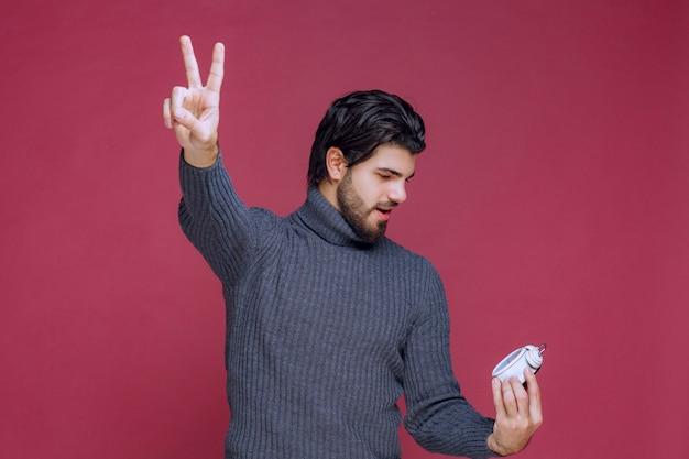 L'uomo che mostra una sveglia bianca e un punto paking a una migliore offerta.