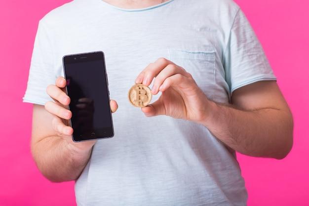 Человек показывает деревянный биткойн и пустой экран мобильного телефона крупным планом