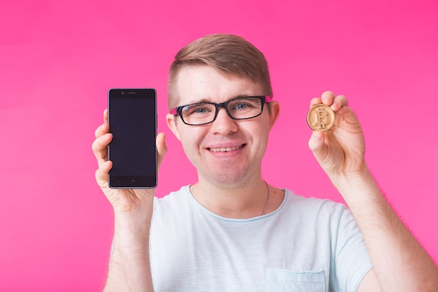 Man showing wooden bitcoin and blank screen mobile phone