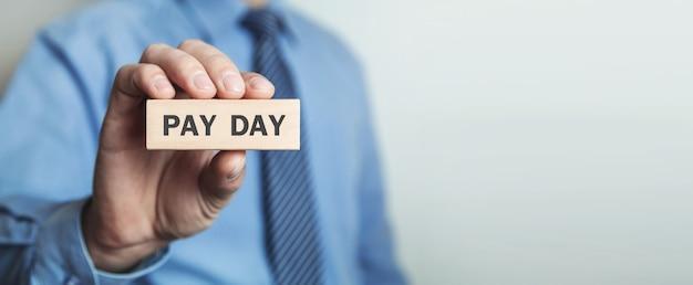 木製のブロックを示す男。給料日。ビジネスコンセプト
