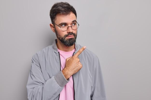 Мужчина показывает место для рекламы, демонстрирует промо-предложения в правом верхнем углу, носит круглую куртку с очками, изолированную на сером