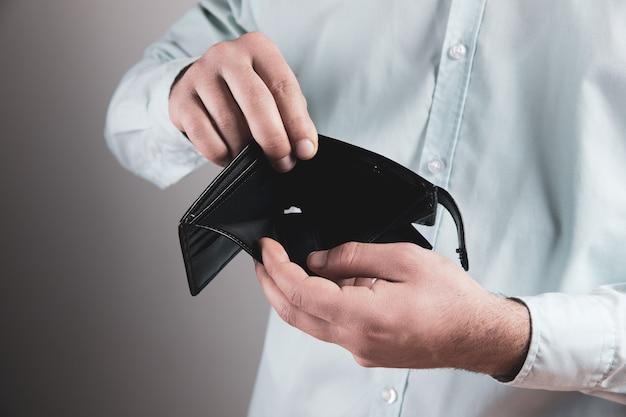 Мужчина показывает пустой кожаный бумажник.