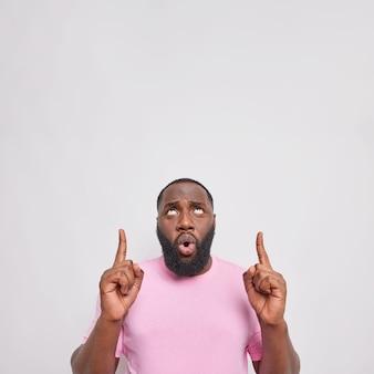 Мужчина показывает точки баннера выше на копировальном пространстве, демонстрирует новую скидку, одетую в повседневную розовую футболку
