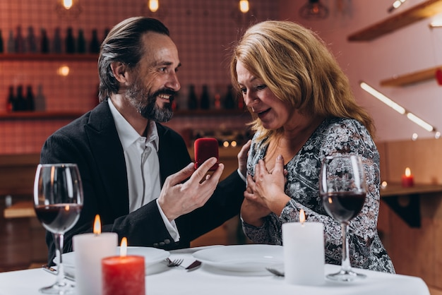 Man shows a box with a wedding ring to an enthusiastic woman during dinner at a restaurant