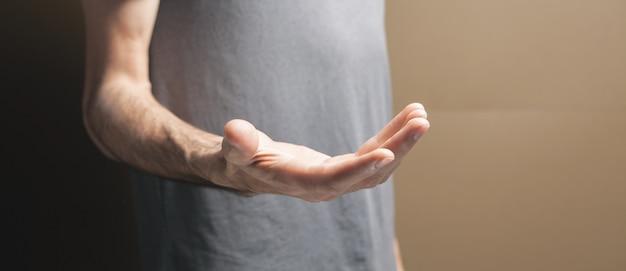 男は茶色の背景に空の手のひらを示しています