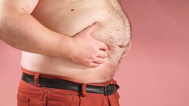 Человек показывает лишний жир на животе. боковой вид крупным планом