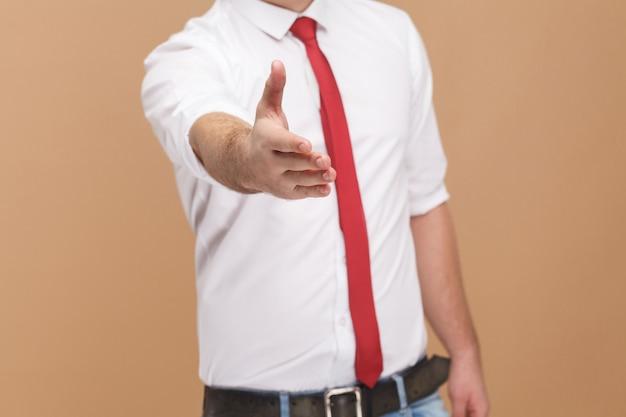 Человек показывает знак рукопожатия и приветствует новую работу. концепция деловых людей, хорошие и плохие эмоции и чувства. студийный снимок, изолированные на светло-коричневом фоне