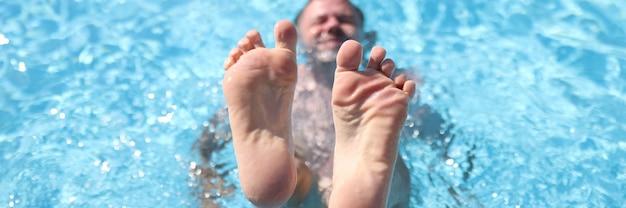 남자는 수영장에 누워있는 동안 그의 발을 보여줍니다