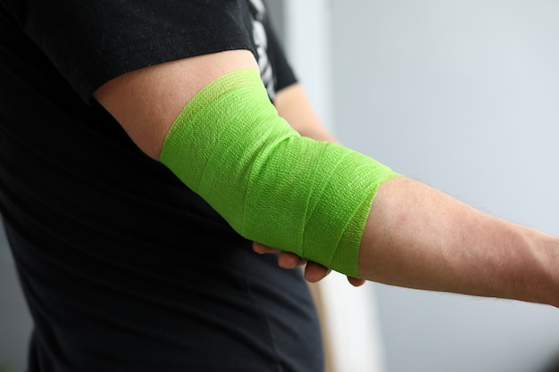 Man shows stretching on arm with elastic bandage.