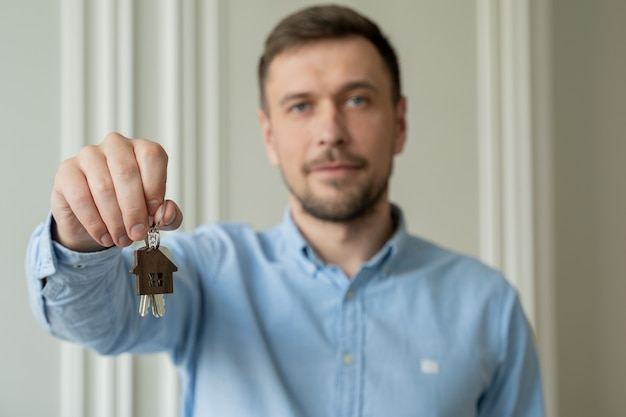 Мужчина показывает ключи от своей новой квартиры в гостиной