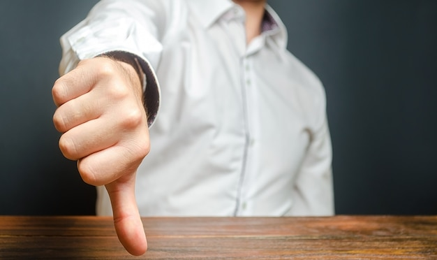 A man shows a thumb down. gesture of disapproval and rejection. bad assessment, harsh criticism