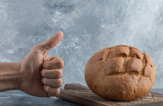 L'uomo mostra il pollice fino alla pagnotta di pane di segale. foto di alta qualità