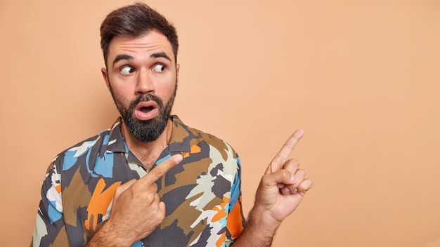 Мужчина показывает неожиданное откровение, указывающее на промо-шоу, копировальное пространство носит красочную рубашку, изолированную на бежевом