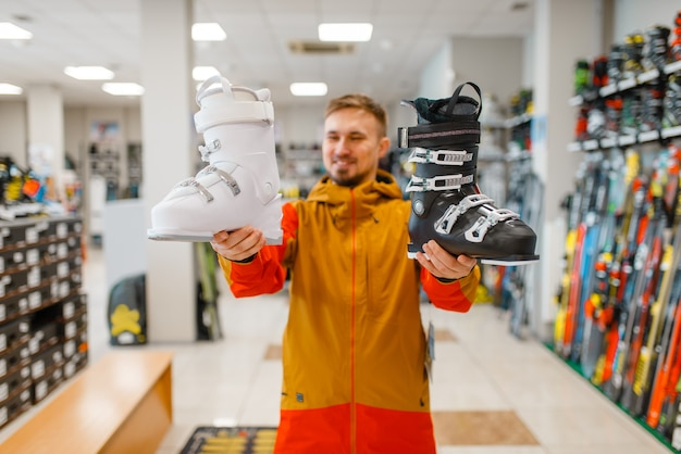 Man shows white and black ski or snowboarding boots in sports shop. winter season extreme lifestyle, active leisure, male customer with protect equipment