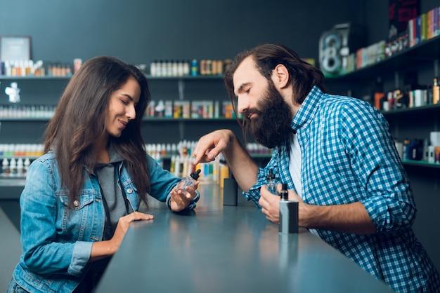Мужчина показывает женщине, как заправлять сигаретную заправку.