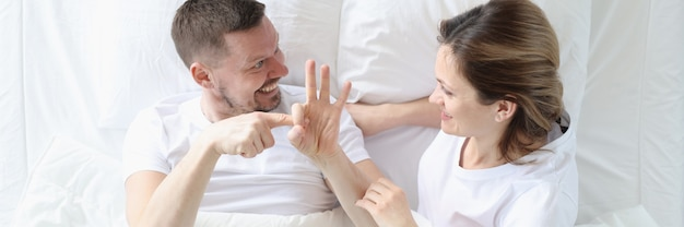 Man shows woman intimate gestures on bed sexual life of partners concept