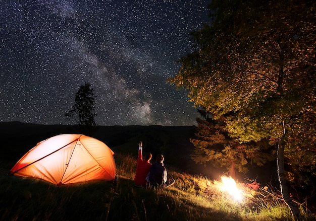 Man shows woman up on evening starry sky at milky way near tent and bonfire on mountains