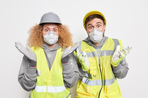 均一な安全呼吸器とヘルメットに身を包んだ男の肩をすくめる肩をすくめる家の改善に取り組む塗装の準備