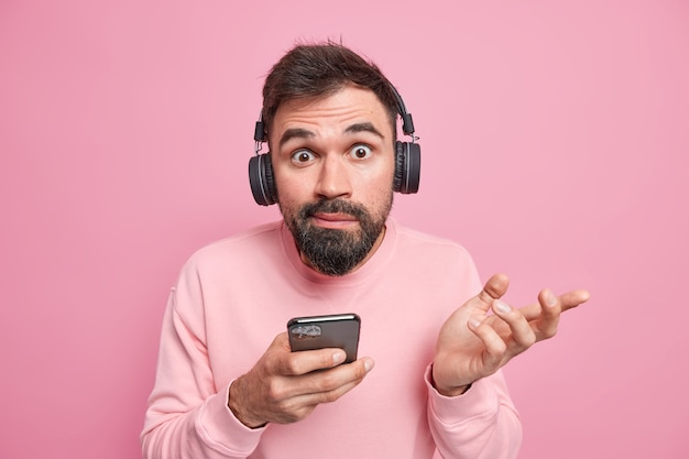 Man shrugs shoulders doesnt know how download new application on phone uses digital devices in modern life wears wireless headphones on ears poses against pink wall